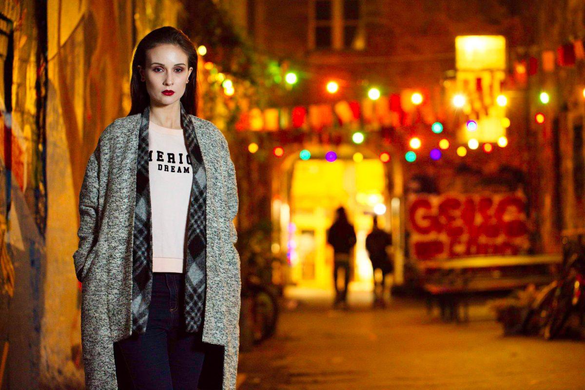Lorena in Ihrem Lieblingssweatshirt und einer langen Strickjacke kombiniert mit Hüftjeans...
